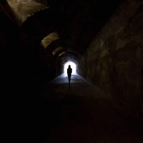 "Person in dark tunnel going towards the light. Hope fear ""afterlife"" concepts"
