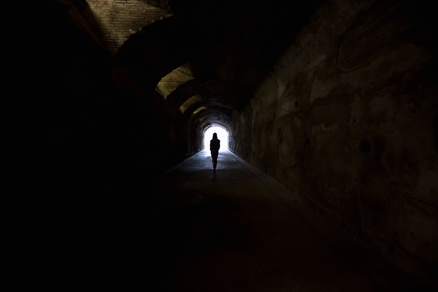 """Person in dark tunnel going towards the light. Hope fear """"afterlife"""" concepts"""