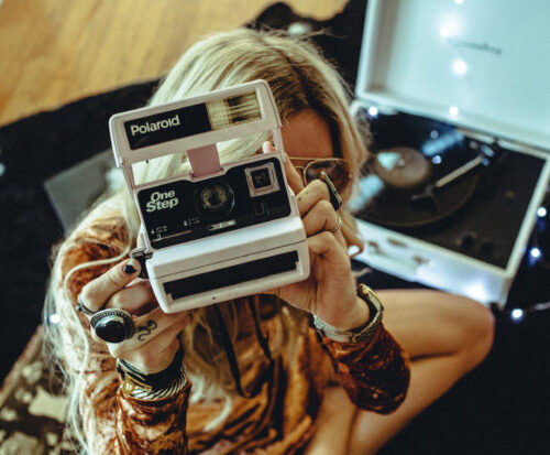 Woman holding vintage Polaroid camera