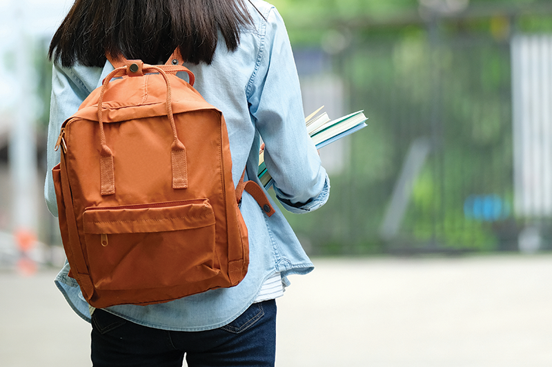Student with backpack carrying books outside
