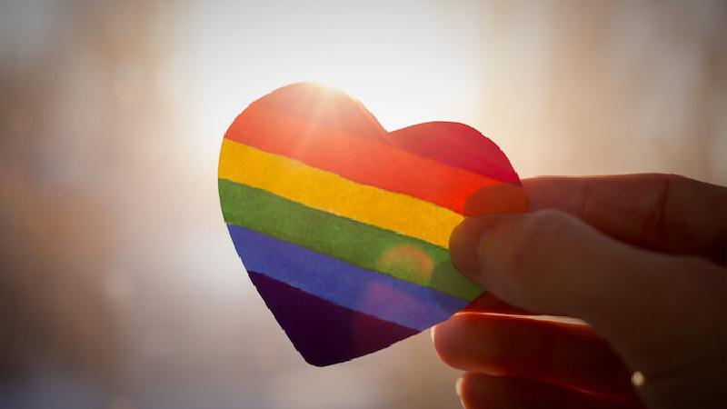 Hand holding LGBTQ rainbow colored heart